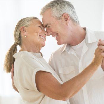 Romantic senior couple dancing at home