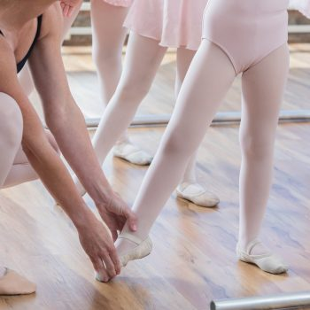 All are unrecognizable as an adult ballet instructor squats beside her young student to physically guide her in pointing her toes at the floor.