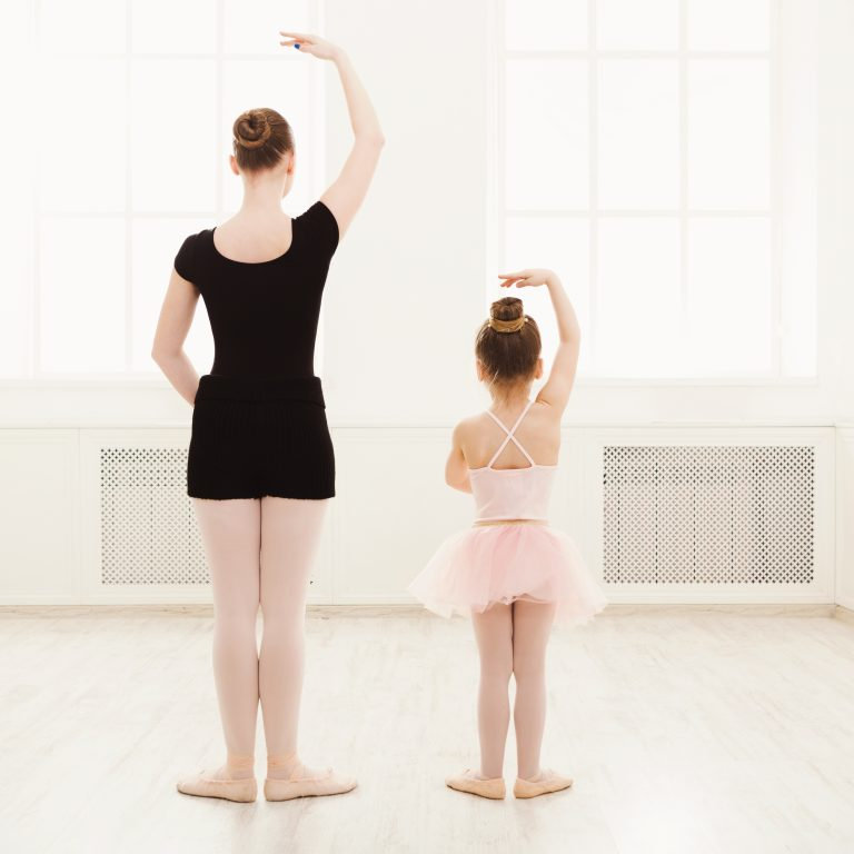 Little girl learning ballet with teacher copy space. Cute small ballerina training classical dance exercises with female coach, back view