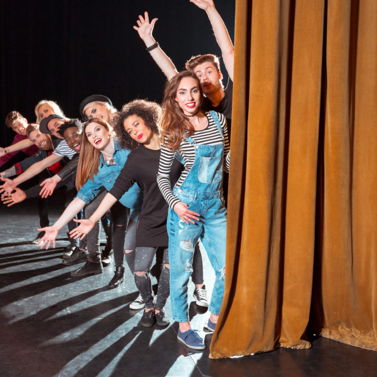 Group of young performers on the stage standing in the line behind the curtain, raising hands.