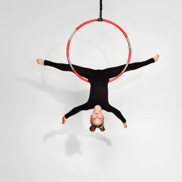 Little acrobat girl in black sportwear doing twine on an aerial hoop